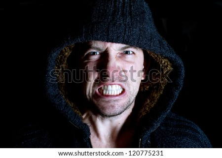 angry violent man with hood up screaming