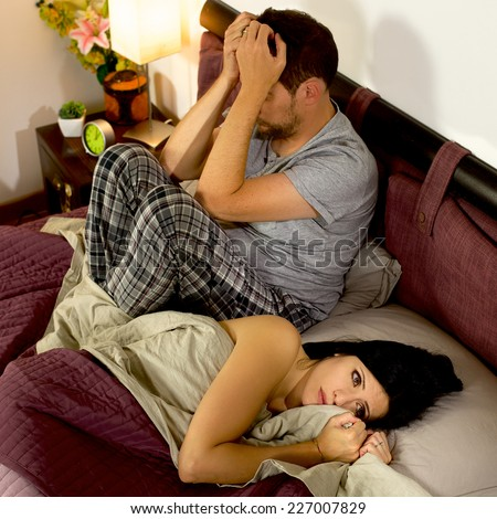 Angry wife and husband not talking in bed - stock photo