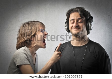 Angry wife screaming against a serene husband listening to music - stock photo