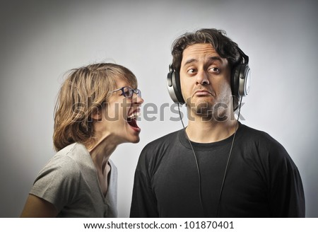 Angry wife screaming against her husband not listening to her wearing headphones - stock photo