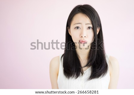 angry woman against pink background - stock photo