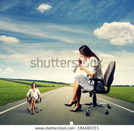 angry woman and calm woman on the chair over dark background - stock photo
