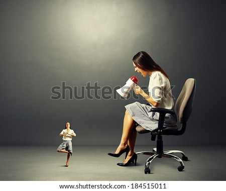 angry woman and small calm woman over dark background - stock photo