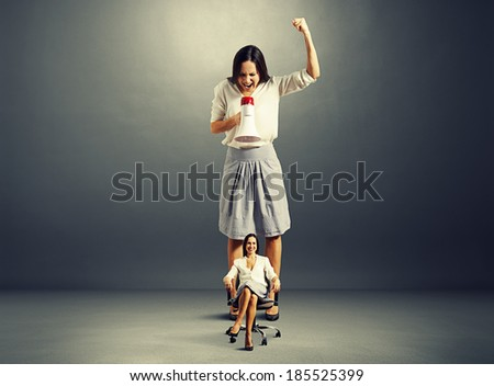 angry woman and smiley calm woman on the chair over dark background - stock photo