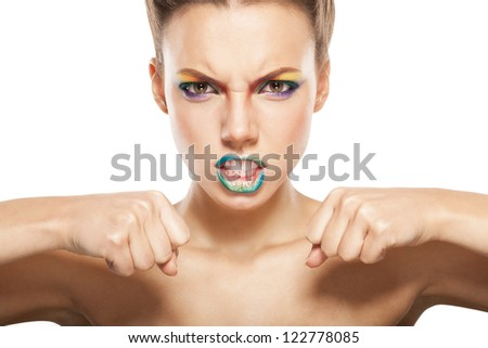 angry woman, beautiful female face with rainbow makeup. - stock photo