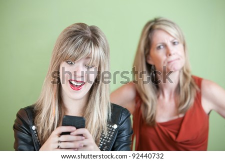 Angry woman behind excited teen on mobile phone - stock photo