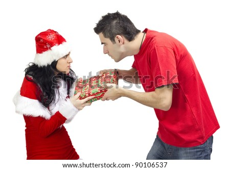 Angry woman dressed in Santa Claus offering a gift to young angry man. - stock photo