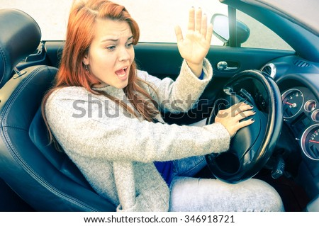 Angry  woman driving convertible car gets mad at motorist - businesswoman using gestures due traffic jam frustration - Red hair girl upset  railing against drivers - Concept of humane frame of mind - stock photo