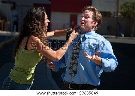 Angry woman helps fix a hapless mans shirt and tie - stock photo
