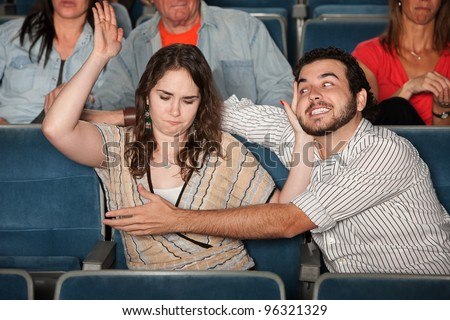 Angry woman hits man trying to grab her in theater - stock photo