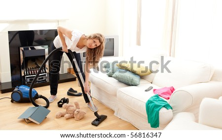 Angry woman in a chaotic living room with vacuum cleaner