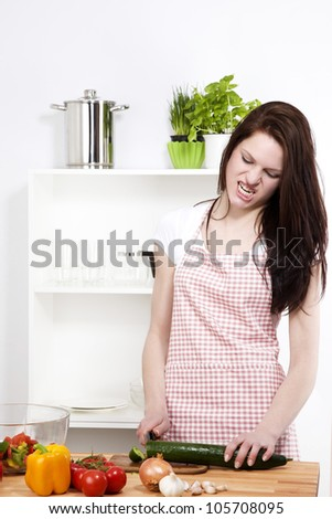 angry woman in a kitchen cutting a cucumber on a chopping board - stock photo