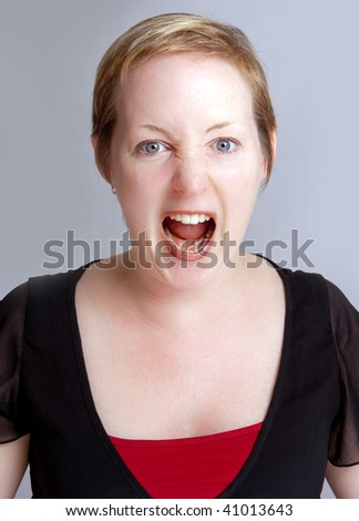 Angry  woman in a shouting fit against a neutral background - stock photo