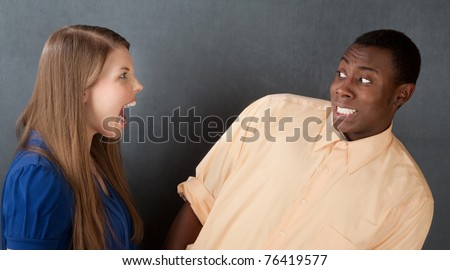 Angry woman in blue dress shouts at attractive African-American male - stock photo