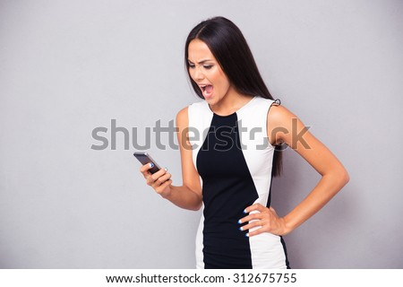 Angry woman in dress shouting on smartphone over gray background - stock photo