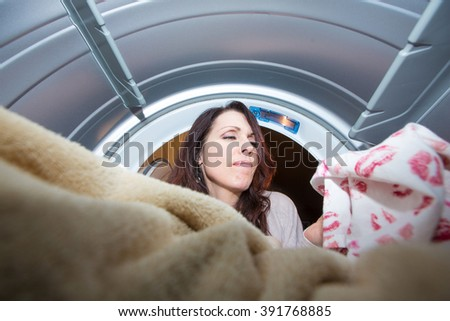 angry woman looking at kiss stained underwear in the dryer - stock photo