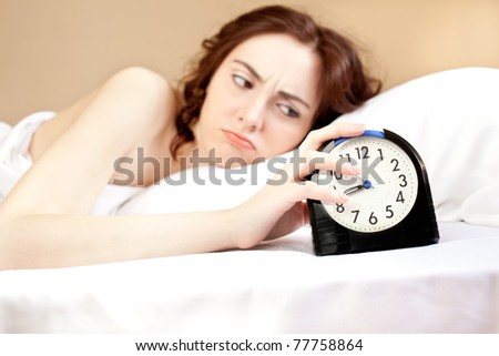 Angry woman lying a bed and holding an alarm (focus on alarm) - stock photo
