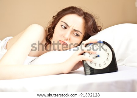 Angry woman lying a bed and holding an alarm (focus on woman) - stock photo