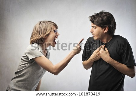 Angry woman pointing her finger against her husband - stock photo