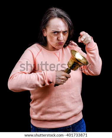Angry woman pointing while ringing a large brass bell. Portrait on black background with copy space. - stock photo