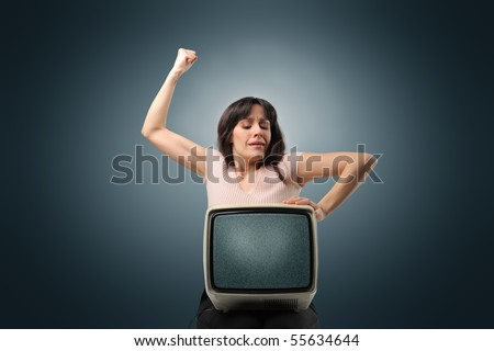 Angry woman punching an old television - stock photo