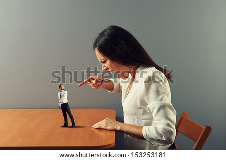 angry woman screaming at startled small man - stock photo