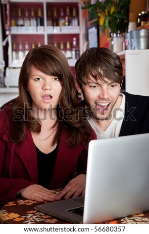 Angry woman shocked with spouse over something on a laptop - stock photo