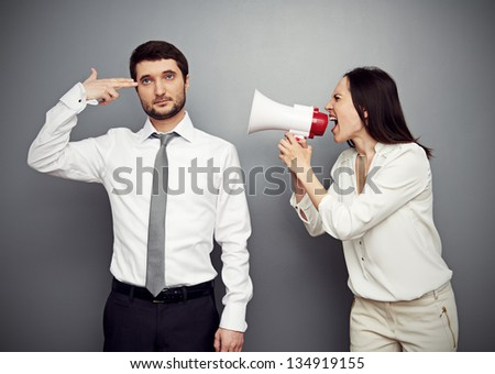 angry woman shouting at the tired man over dark background ...