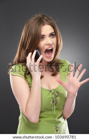 angry woman shouts in phone. Negative emotions on a young face. Studio female portrait - stock photo