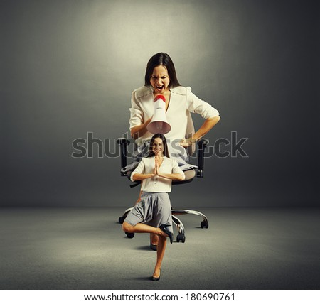 angry woman sitting on the office chair and screaming at small calm woman over dark background - stock photo