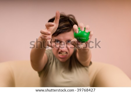 angry woman squeezes a green ball - stock photo