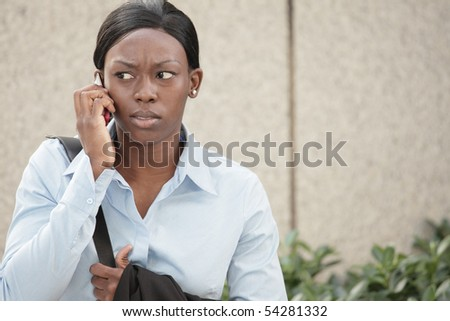 Angry woman talking on the phone - stock photo