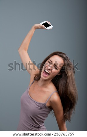 angry woman throwing a mobile phone - stock photo