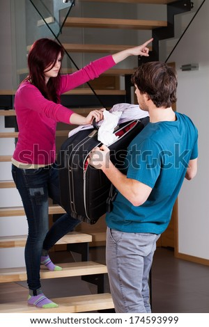 Angry woman throwing man away from home using violence - stock photo