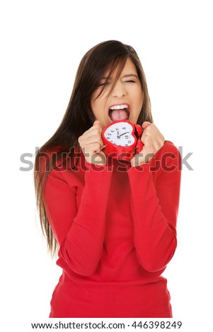 Angry woman with alarm clock. - stock photo