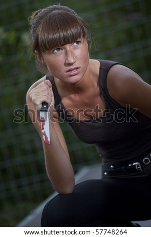 angry woman with bloody knife in her hand outdoor