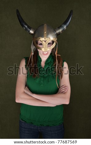 Angry woman with folded arms in Viking helmet - stock photo