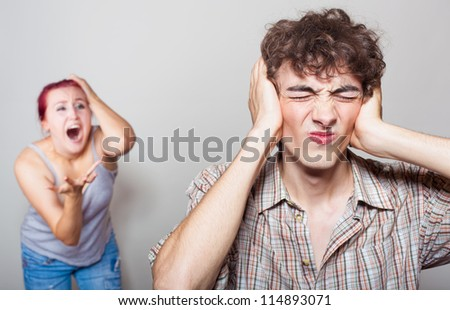 Angry woman yelling at her husband, the unfortunate man closed his ears with his hands - stock photo