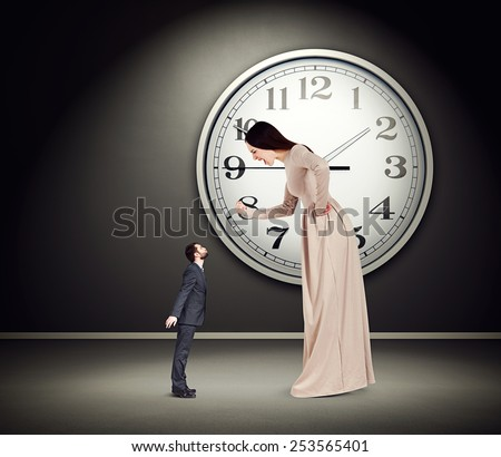 angry yelling woman showing fist and looking at small kissing man. concept photo in empty dark room with big white clock on the wall - stock photo