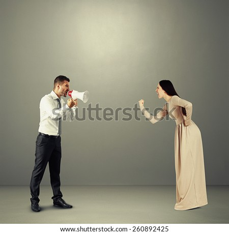 angry yelling woman showing fist to emotional man with megaphone. photo over dark background - stock photo