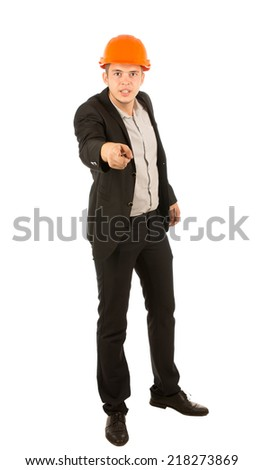 Angry young architect or engineer wearing an orange hardhat glaring at the camera and pointing his finger in blame, full length isolated on white - stock photo