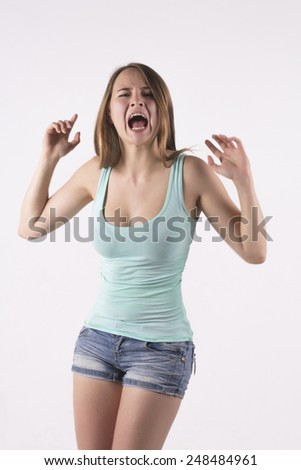 angry young blonde woman screams - stock photo