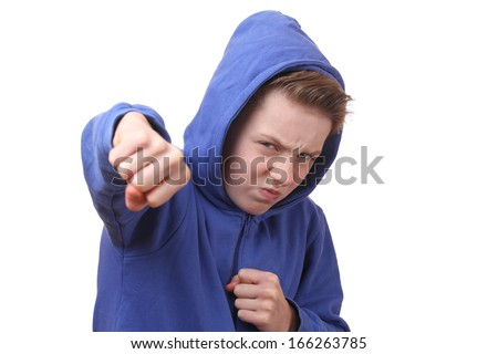 Angry young boy throws a punch - stock photo