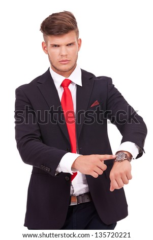 angry young business man is showing you his watch, telling you that you are late. isolated on white background