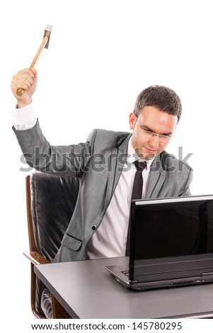 Angry young business man with a hammer ready to smash a laptop over white background - stock photo