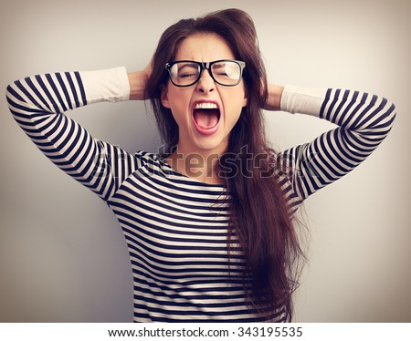 Angry young business woman in glasses strong screaming with wild open mouth and holding head the hands. Toned closeup portrait - stock photo