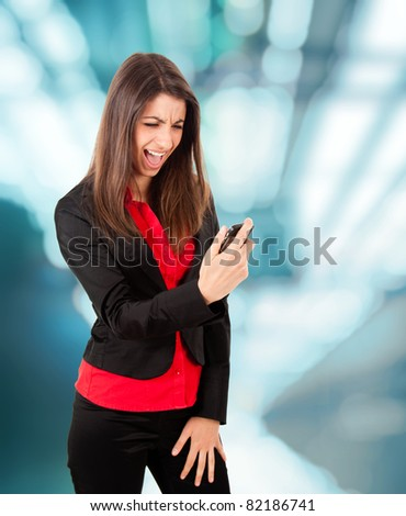 Angry young business woman yelling at her phone - stock photo