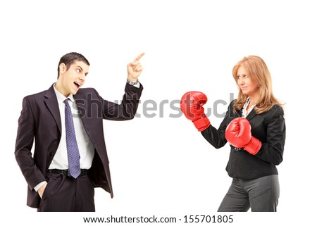 Angry young businessman having an argument with a businesswoman with boxing gloves isolated on white background - stock photo