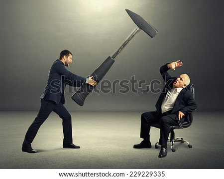 angry young businessman holding big hammer and screaming at frightened senior boss. photo at outdoor - stock photo