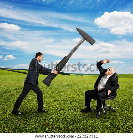 angry young businessman holding big hammer and screaming at senior boss. photo at outdoor